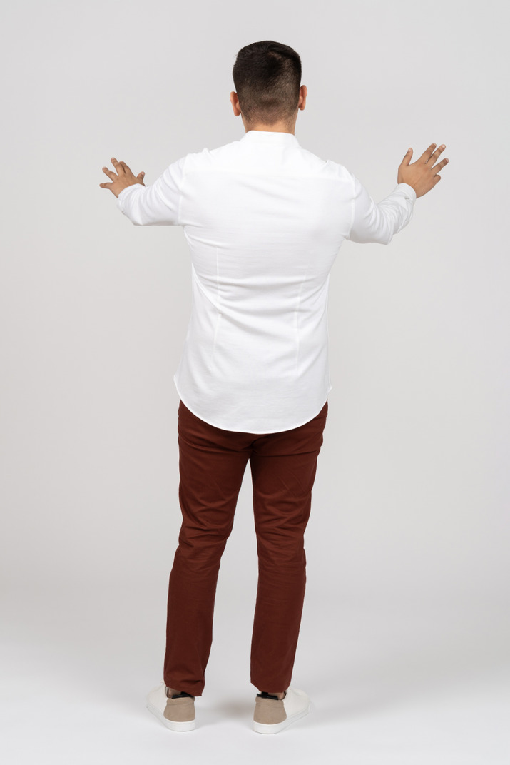 Back view of a young latino man holding out his hands in front of him