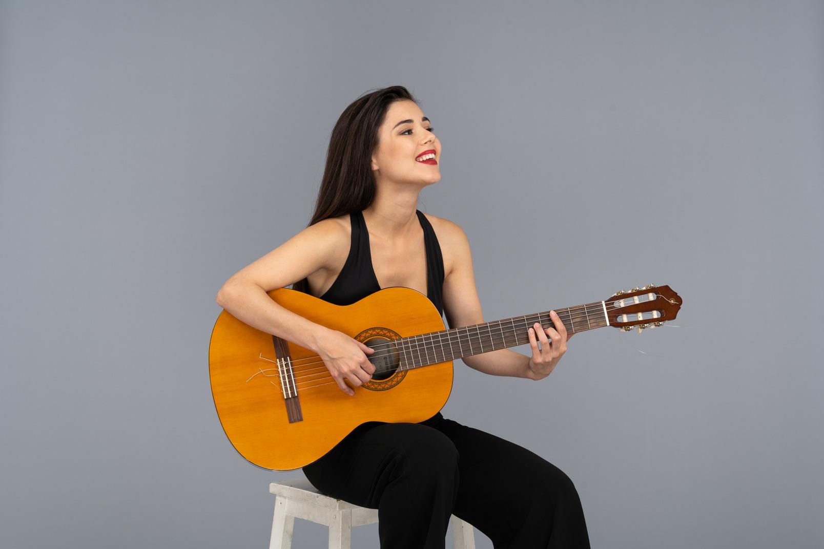 Dreiviertelansicht einer sitzenden lächelnden jungen dame im schwarzen anzug, der gitarre spielt
