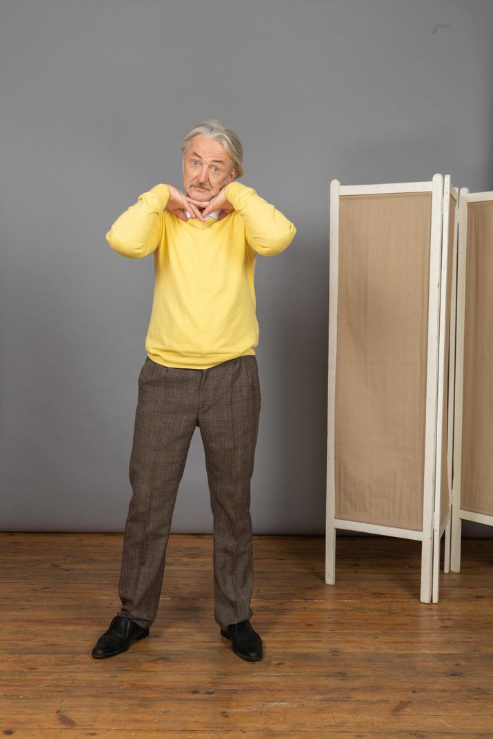 Vorderansicht eines alten mannes, der hände unter kinn legt