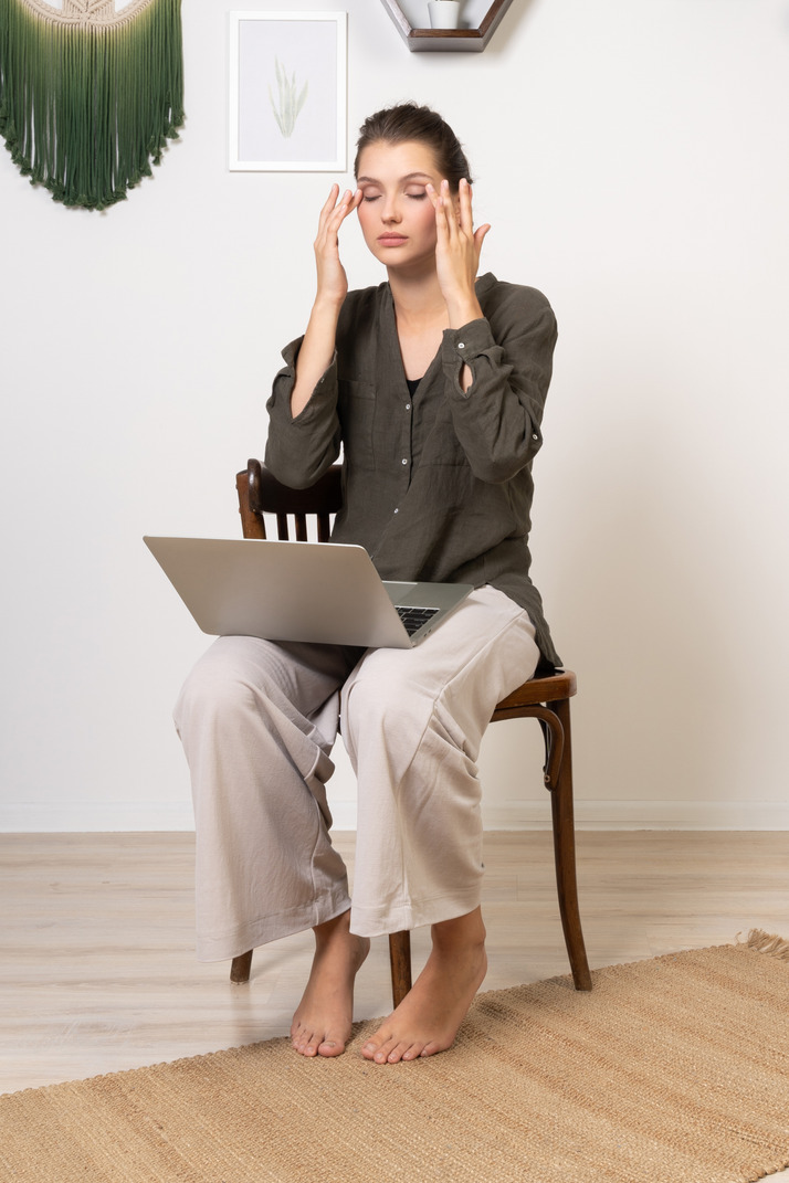 Three-quarter view of a busy young woman with a headache sitting on a chair with a laptop