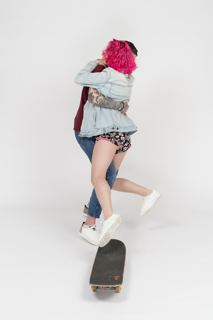 Pink haired girl falling down from a skateboard to her boyfriend`s arms