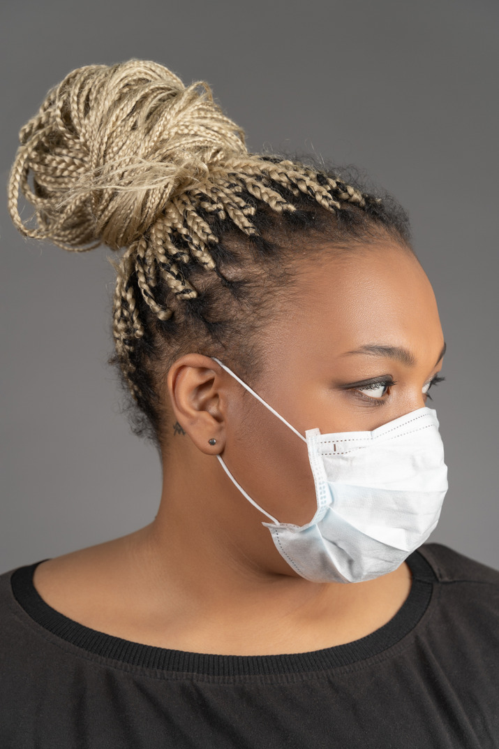 African-american woman in medical mask looking aside