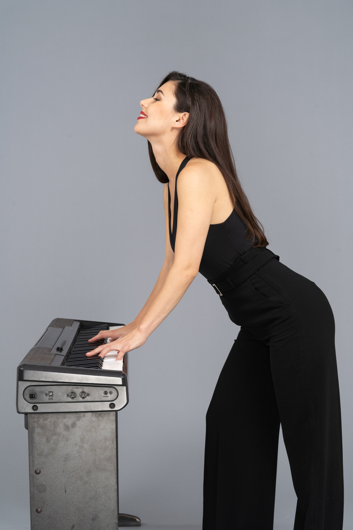 Seitenansicht einer lächelnden jungen dame im schwarzen anzug, der das klavier spielt, während kopf erhöht wird