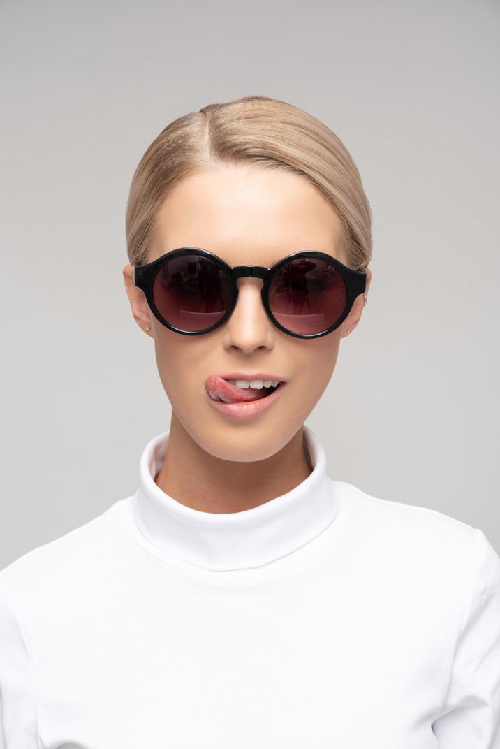 Mujer atractiva con gafas de sol y mostrando su lengua