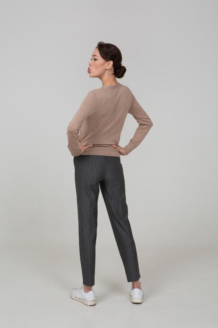 Dreiviertel-rückansicht einer jungen dame in pullover und hose, die schmollt und die hände auf die hüften legt