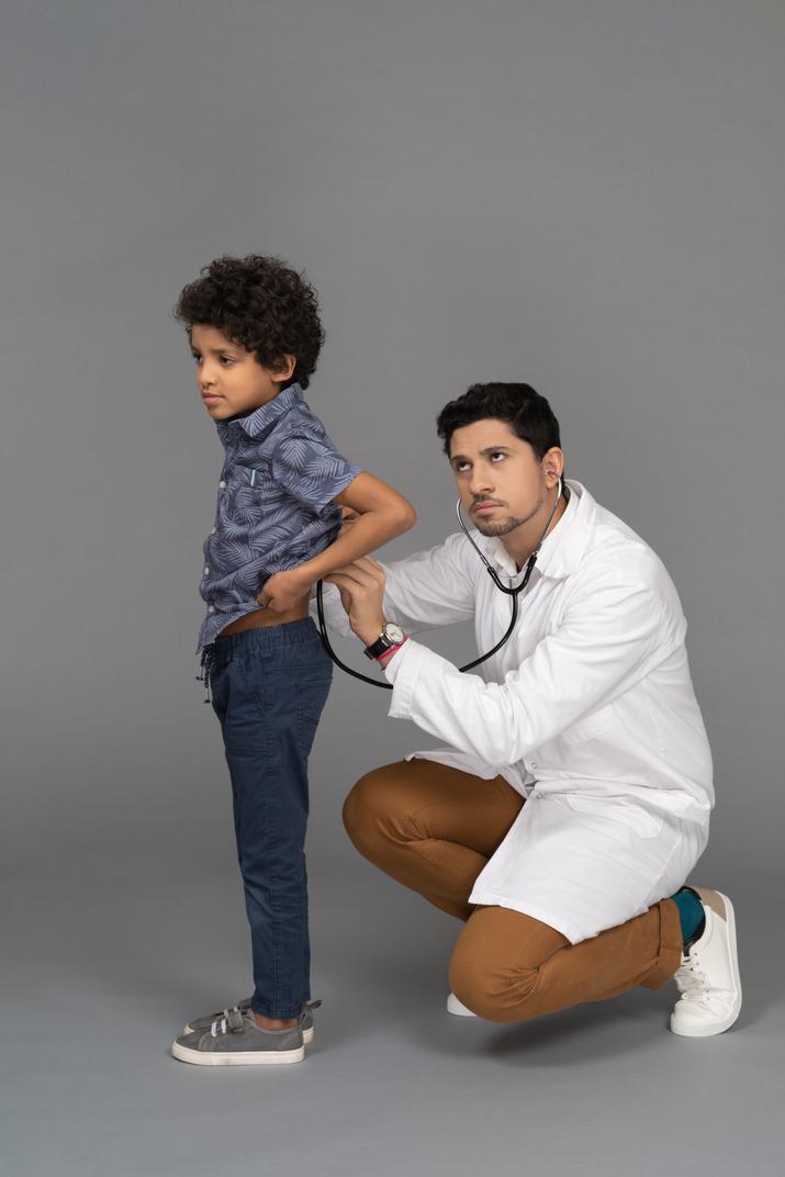 Doctor examining little boy