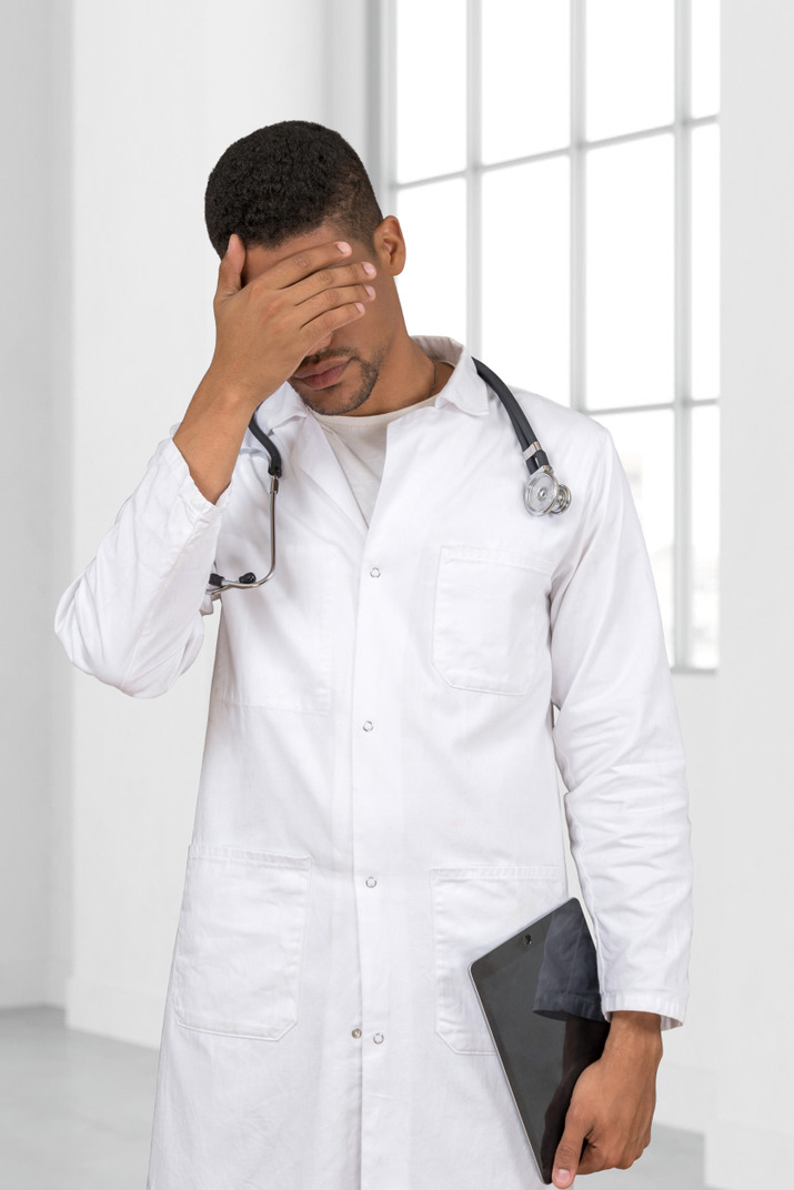 Tired man doctor touching his head