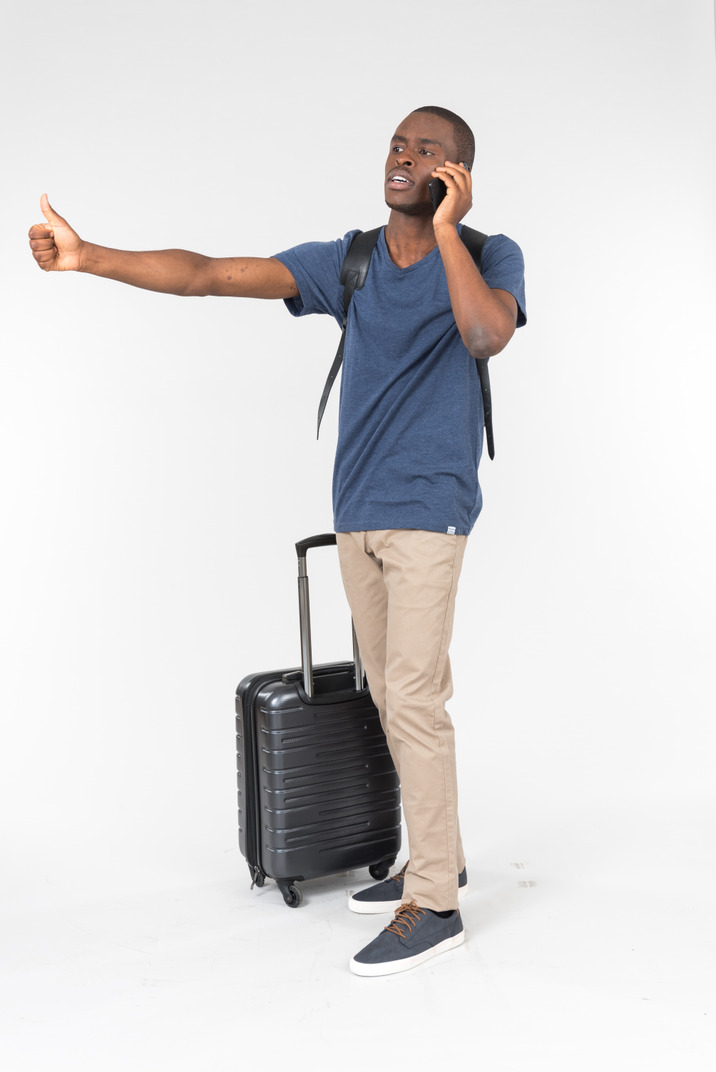 Male traveller talking on the phone and showing thumb up