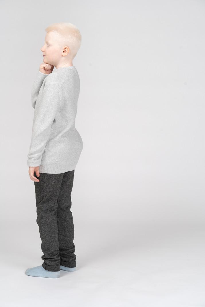Seitenansicht eines blonden jungen in freizeitkleidung, die träumt, während sie kinn berührt