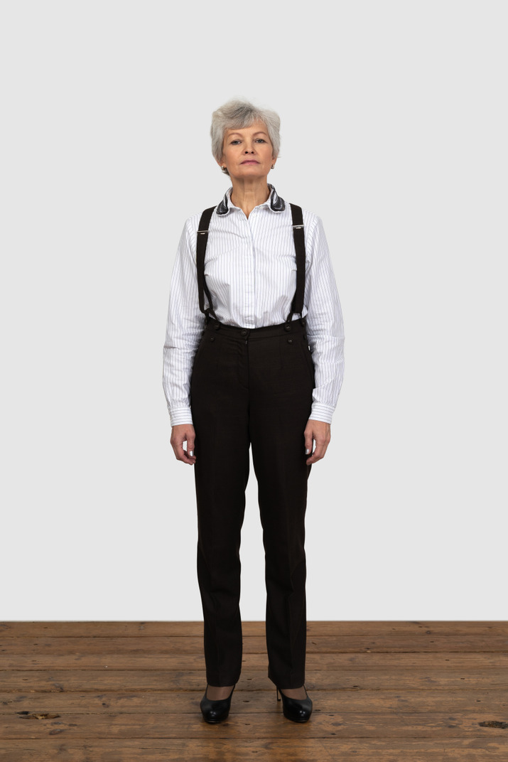 Vorderansicht einer alten frau in bürokleidung, die still im raum steht
