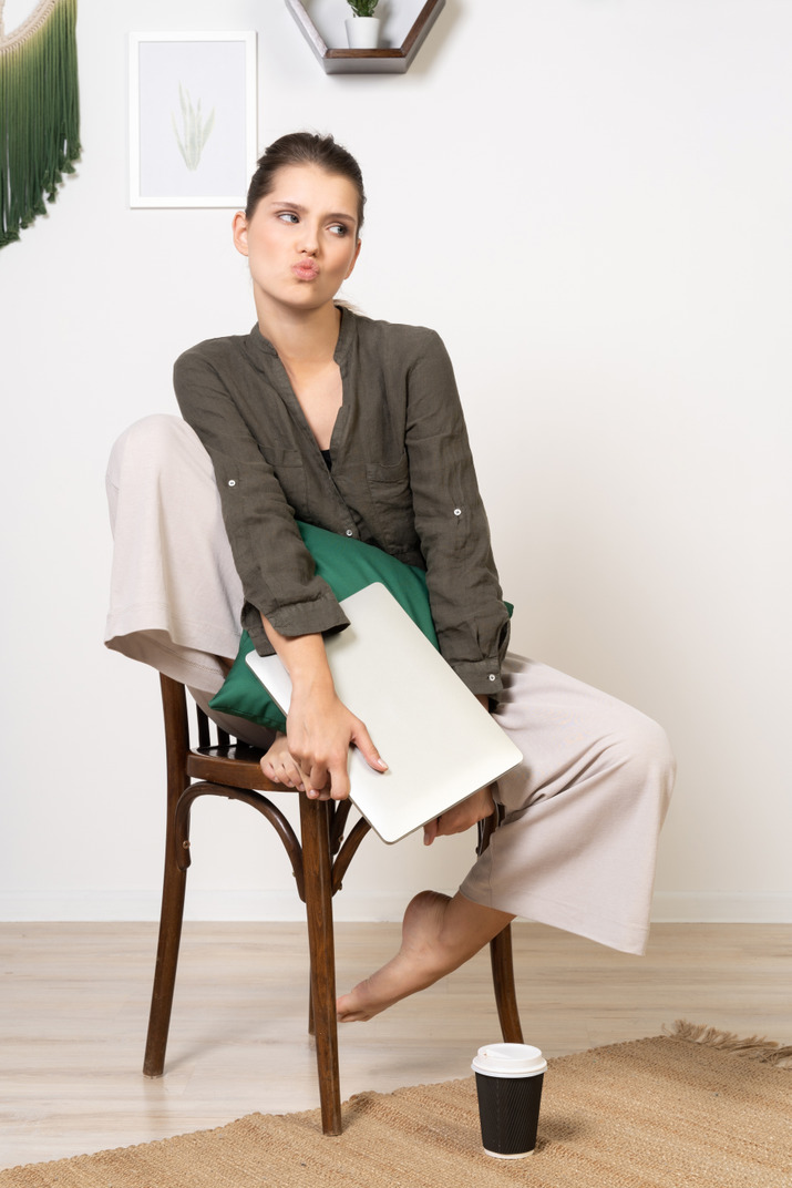 Front view of a pouting young woman sitting on a chair and holding her laptop
