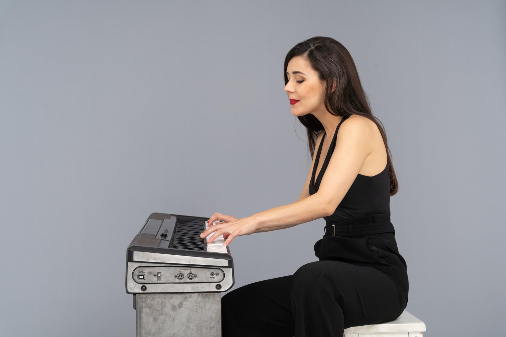 Vista lateral de una joven sentada sonriente en traje negro tocando el piano