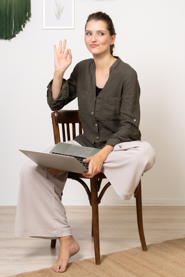Front view of a funny young woman sitting on a chair with a laptop & showing ok gesture