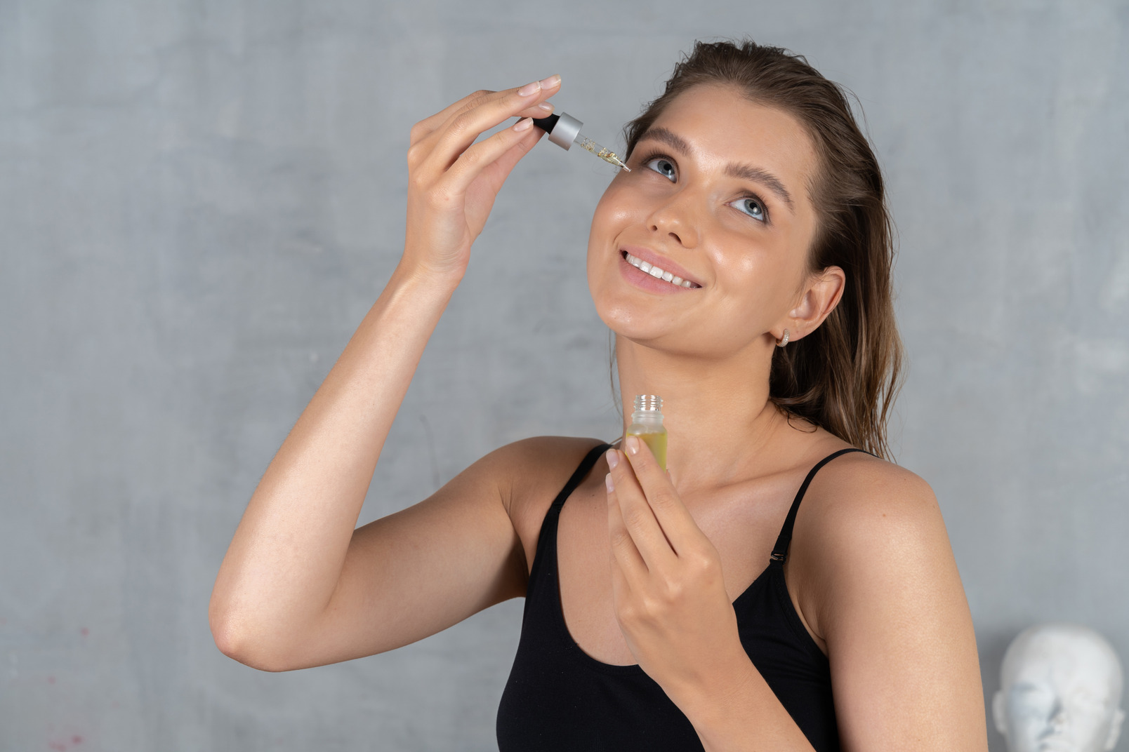Vue de face d'une jeune femme souriante à l'aide de sérum pour le visage