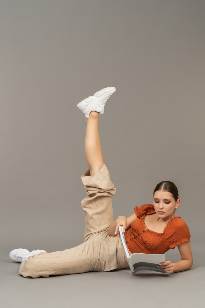Young woman stretching her leg while reading a book