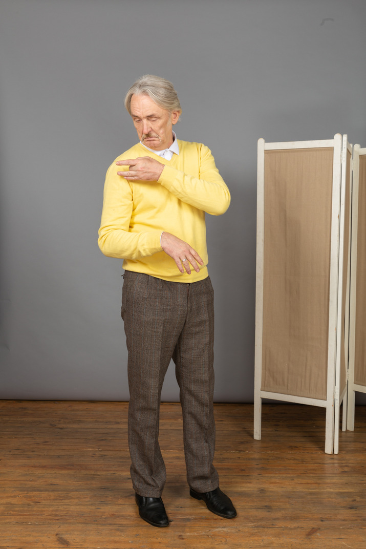 Three-quarter view of an old man touching shoulder