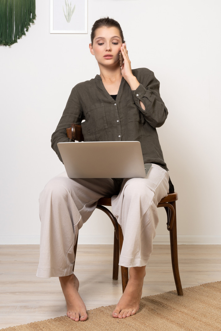 Front view of a busy young woman sitting on a chair with a laptop & mobile