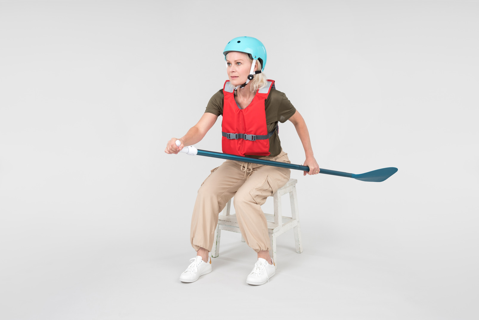 Mature woman in life vest and blue helmet holding paddle