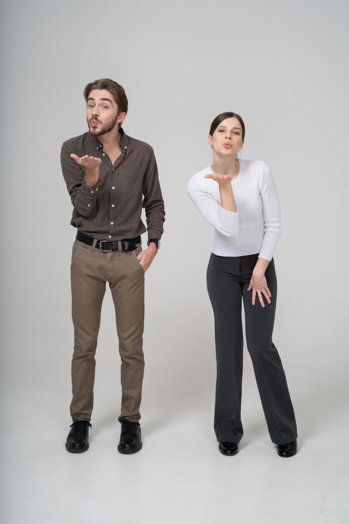 Vorderansicht eines jungen paares in bürokleidung, das einen luftkuss sendet