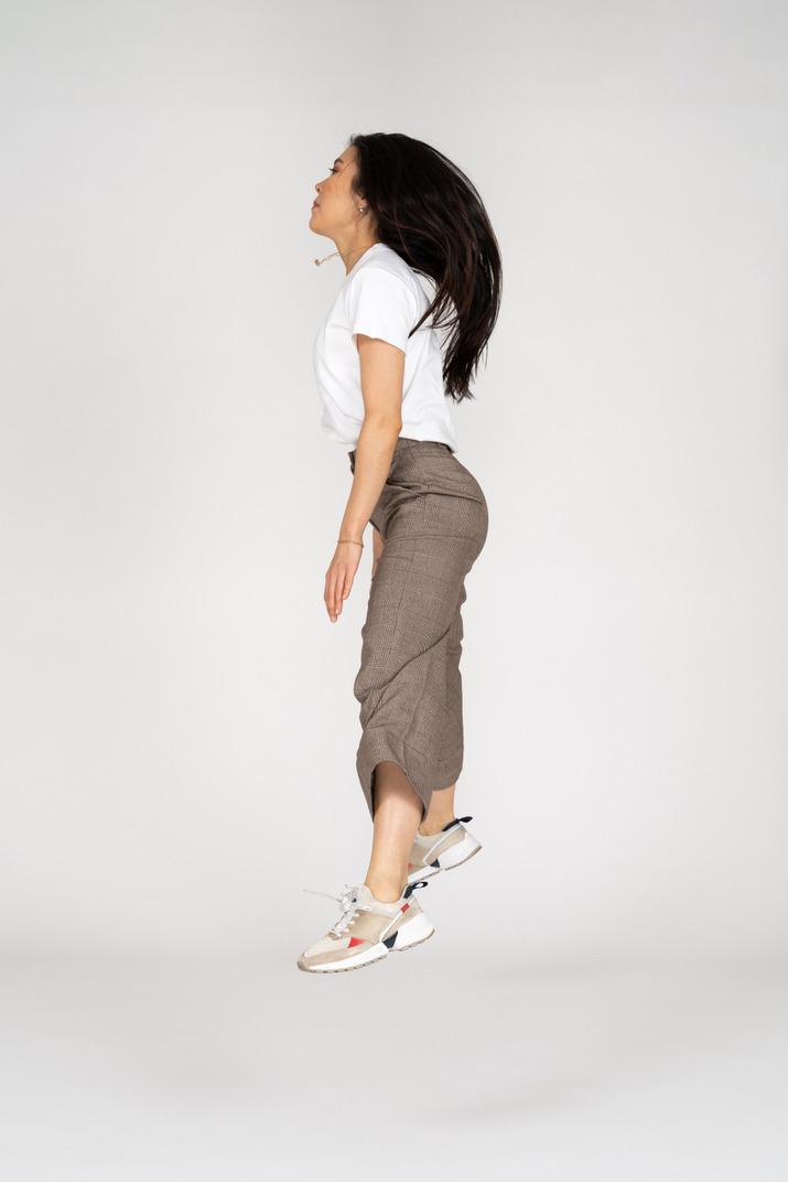Seitenansicht einer springenden jungen dame in reithose und t-shirt, die ihre beine ausbreitet
