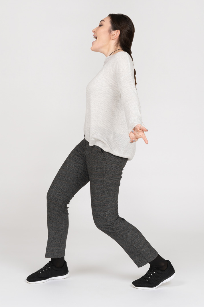 Happy young woman walking sideways with her hands wide open