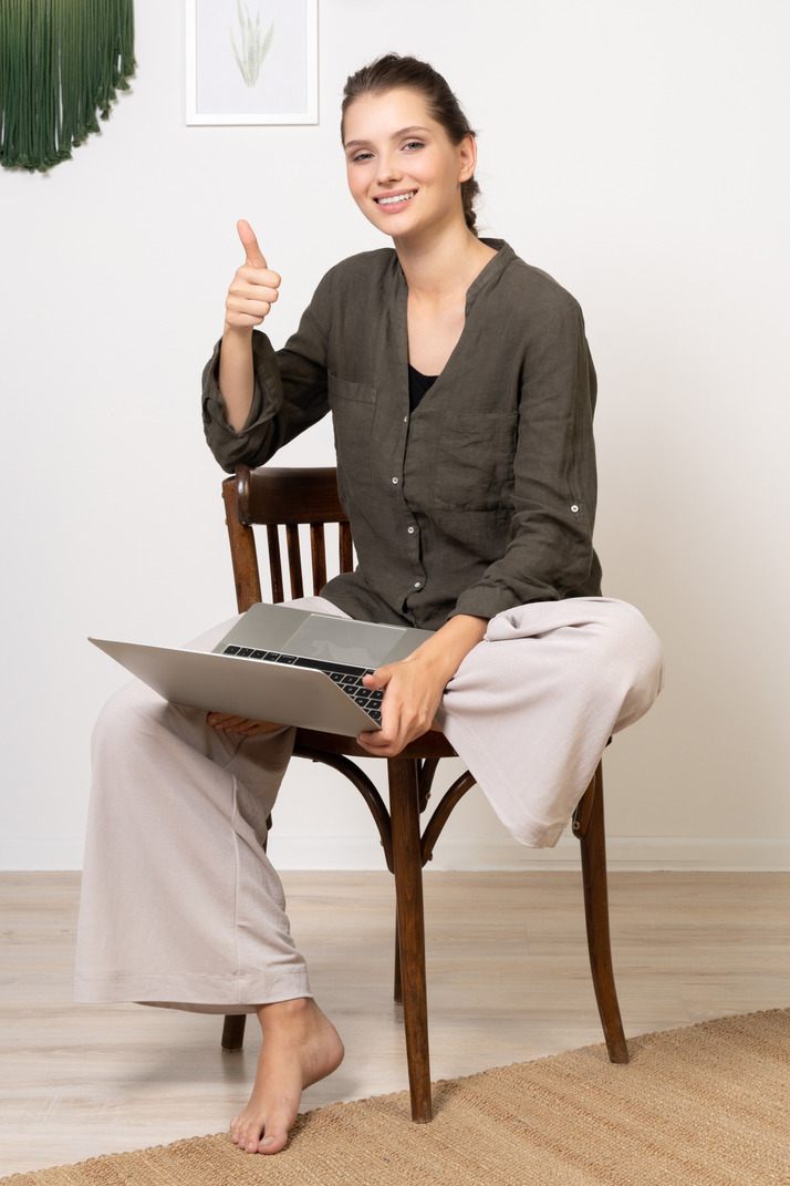 Front view of a smiling young woman sitting on a chair with a laptop & showing thumb up