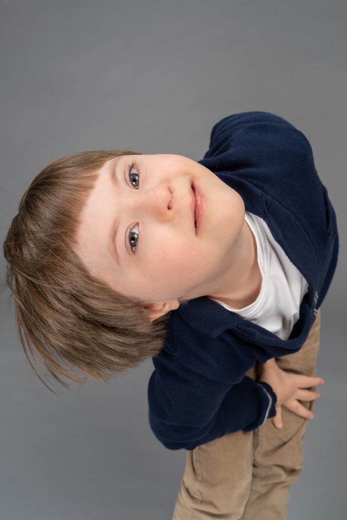 Fröhlicher kleiner junge, der nach oben schaut