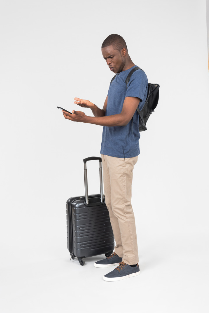 Outraged male tourist standing near luggage and looking at smartphone