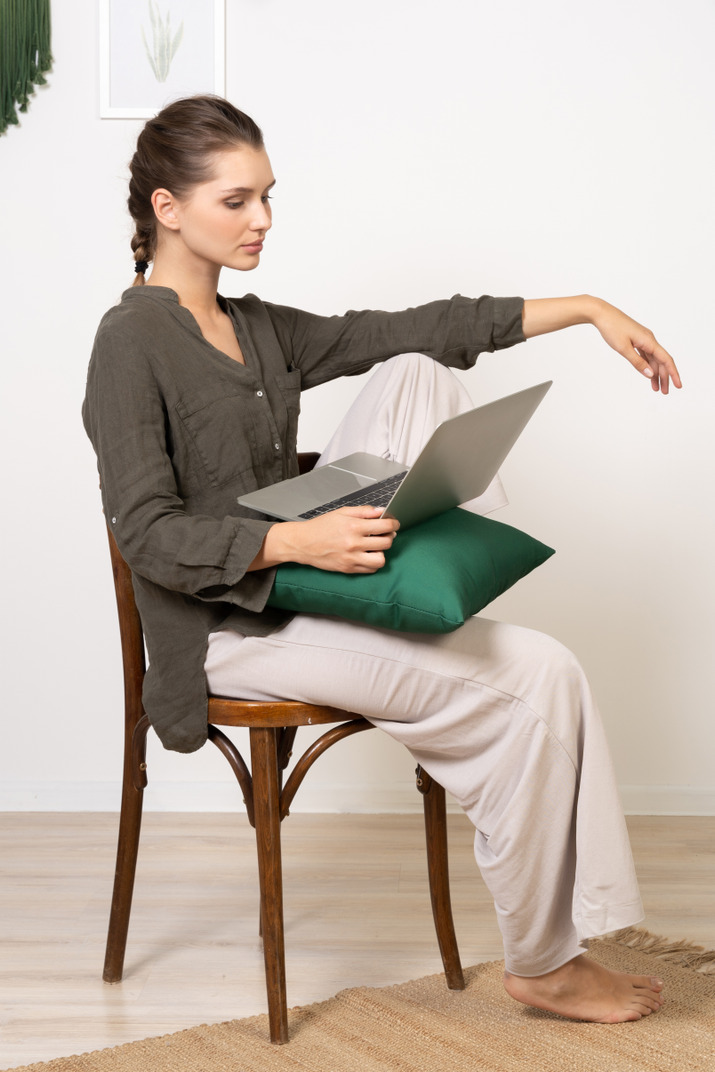 Side view of a young woman wearing home clothes sitting on a chair with a laptop