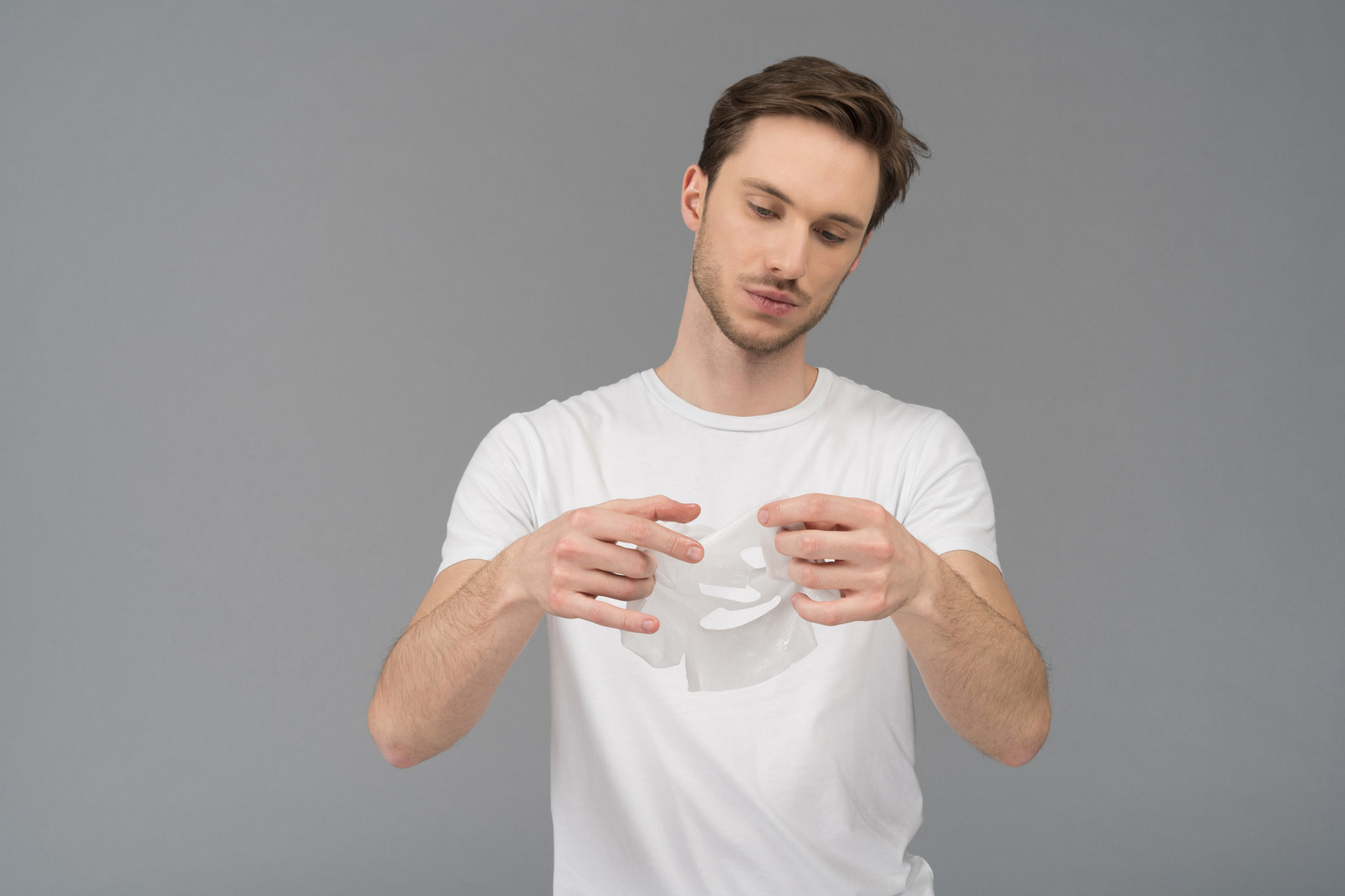 Front view of a young man unfolding facial mask