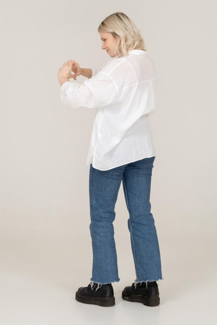 Dreiviertel-rückansicht einer blonden frau in freizeitkleidung, die eine herzgeste zeigt