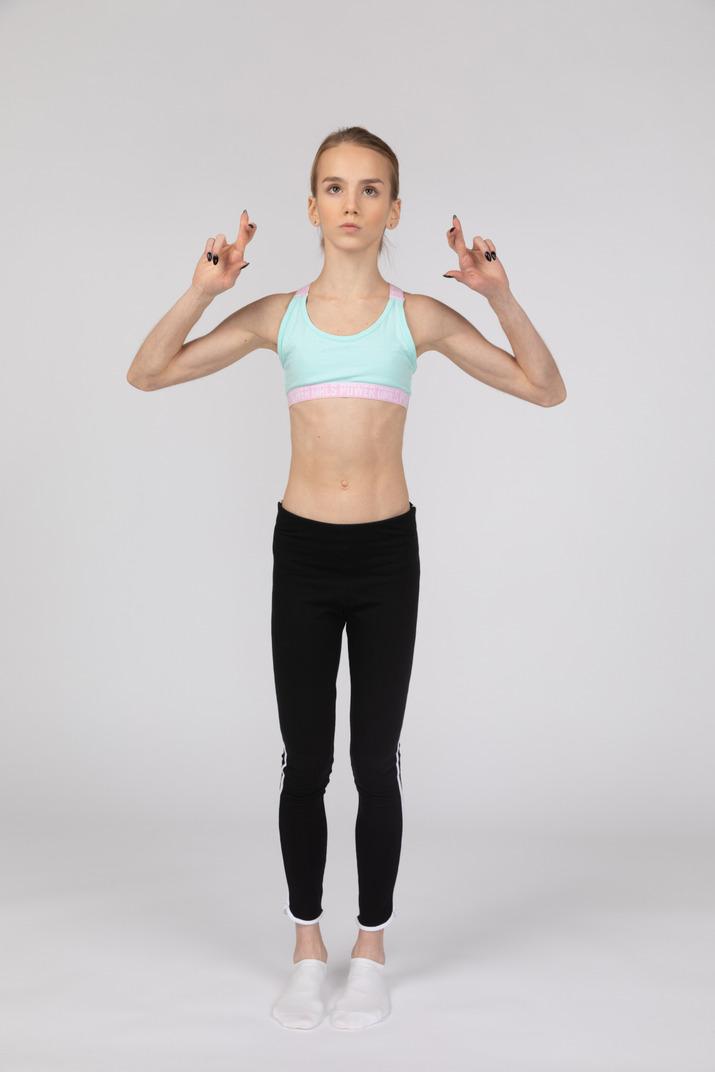 Front view of a teen girl in sportswear crossing fingers
