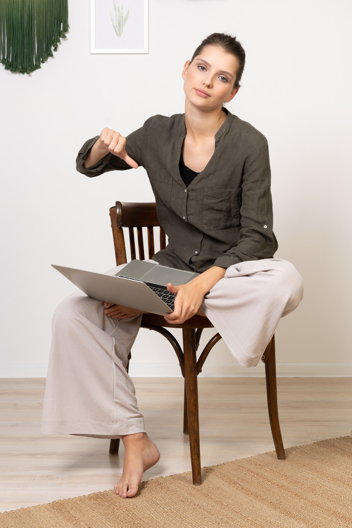 Front view of a displeased young woman sitting on a chair with a laptop & showing thumb down