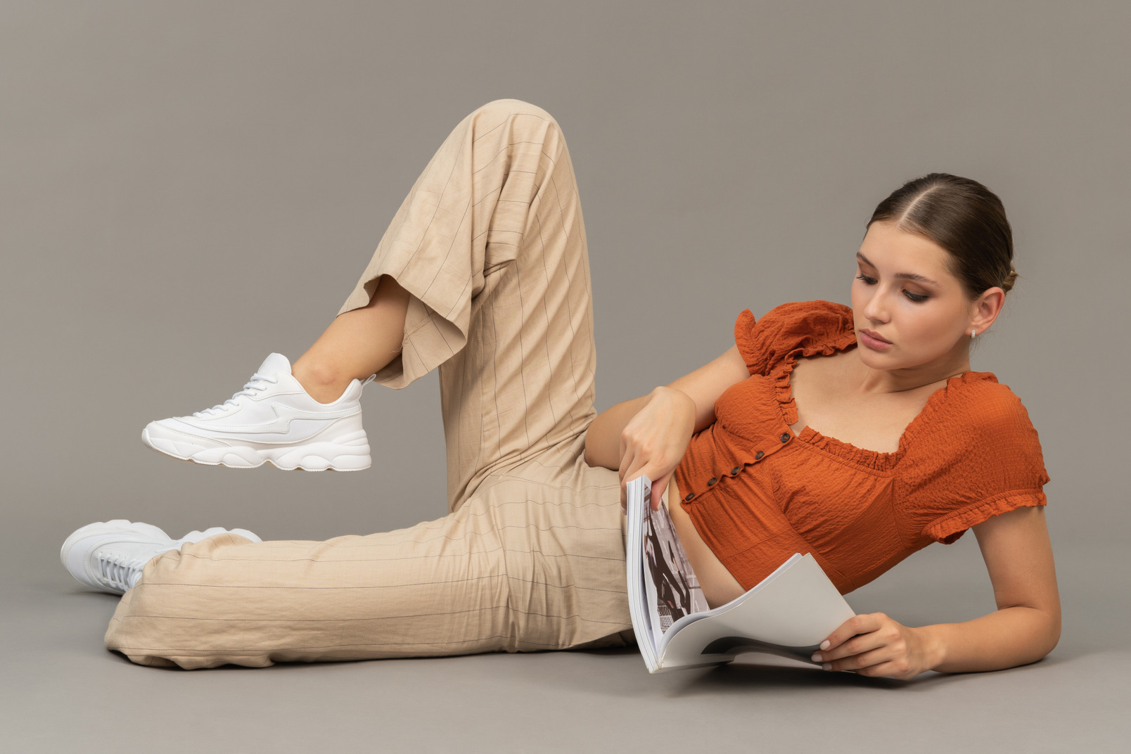 Young woman lying down and reading