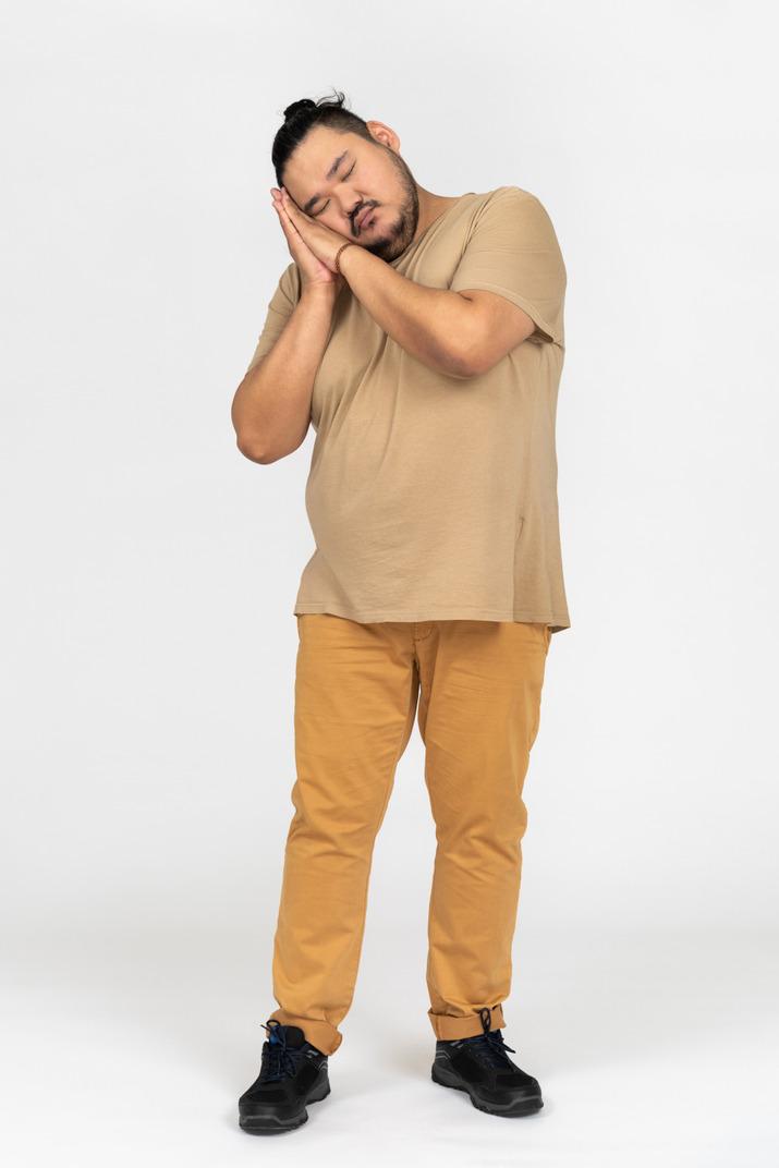 Plump asian man keeping eyes closed and making a sleep gesture