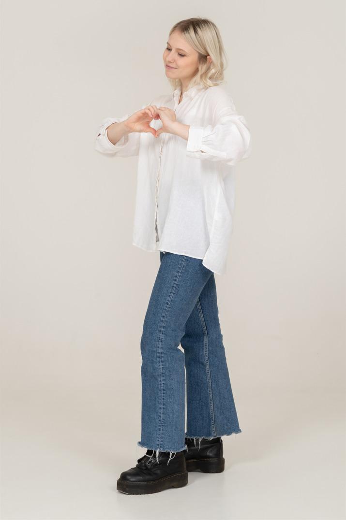 Dreiviertelansicht einer blonden frau in freizeitkleidung, die eine herzgeste zeigt und lächelt