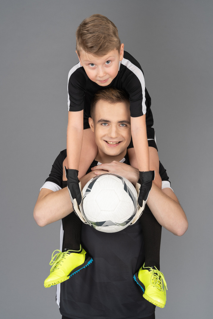 Close-up of a football player holding little boy on his neck
