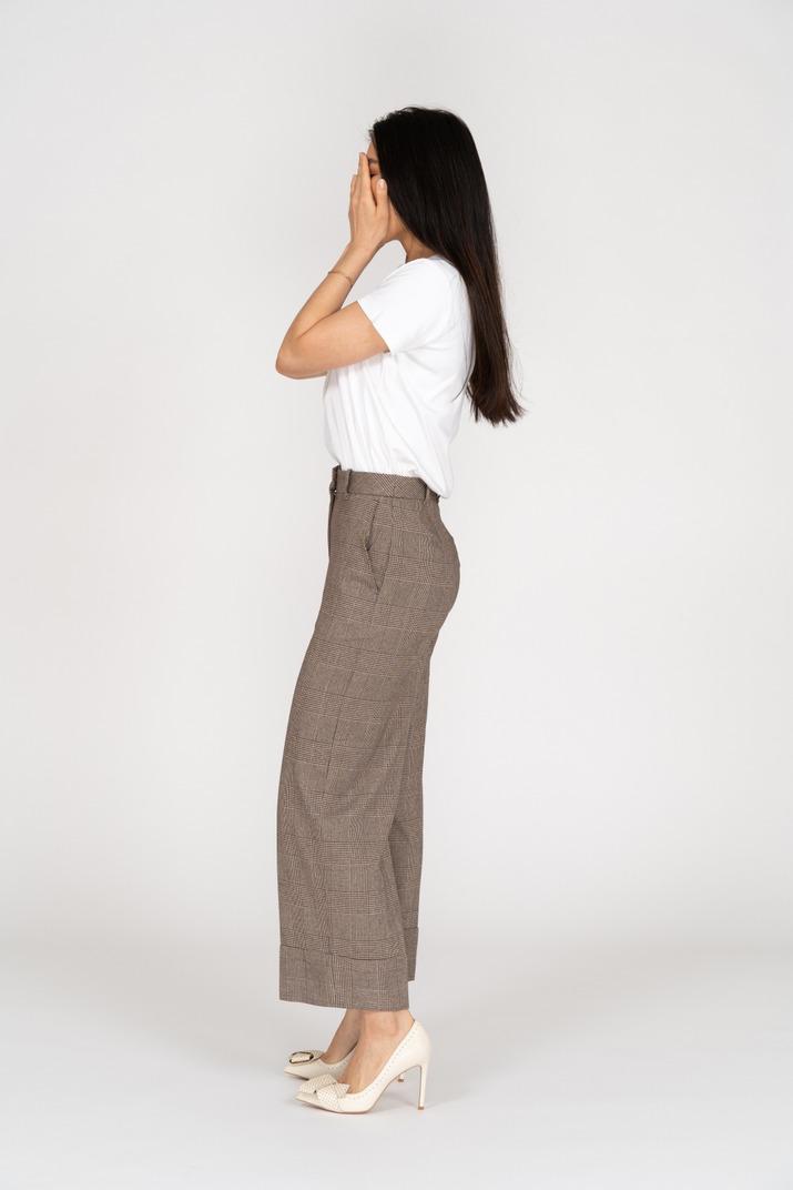 Seitenansicht einer jungen dame in reithose und t-shirt, die ihr gesicht versteckt