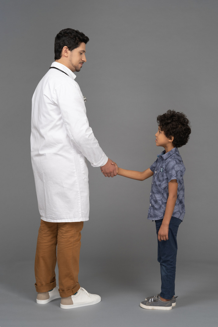 Boy and doctor shacking hands
