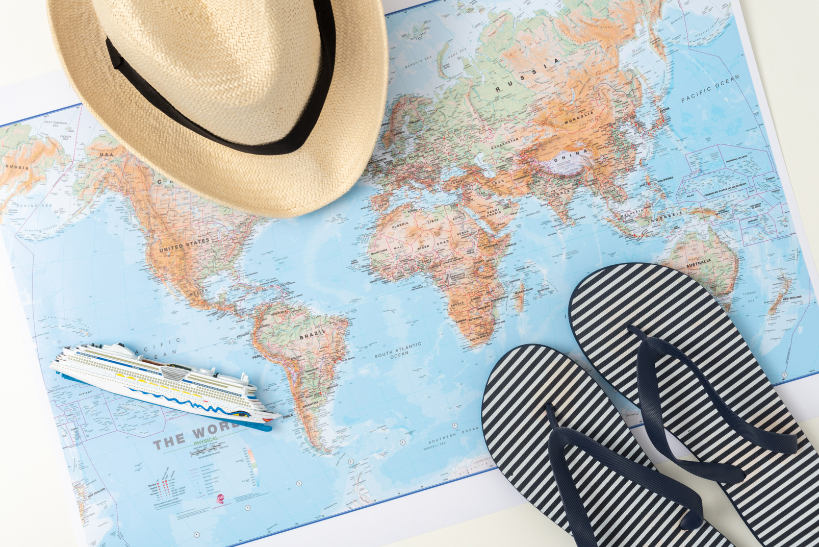 A straw hat, a map and flip-flops, aka every summer tourist's starter pack