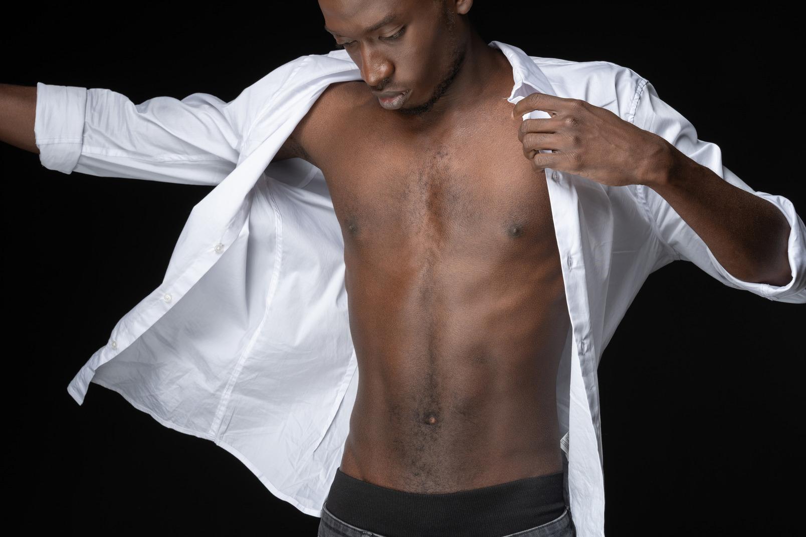 Kontrastbild eines jungen mannes, der im dunkeln einen weißen schuss anlegt