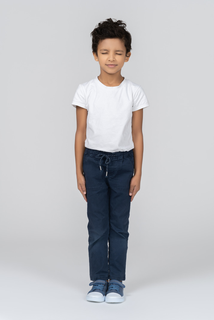 A boy standing with hands alongside body