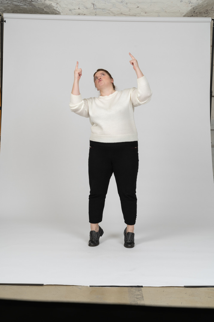Front view of a plump woman in casual clothes standing with raised arms