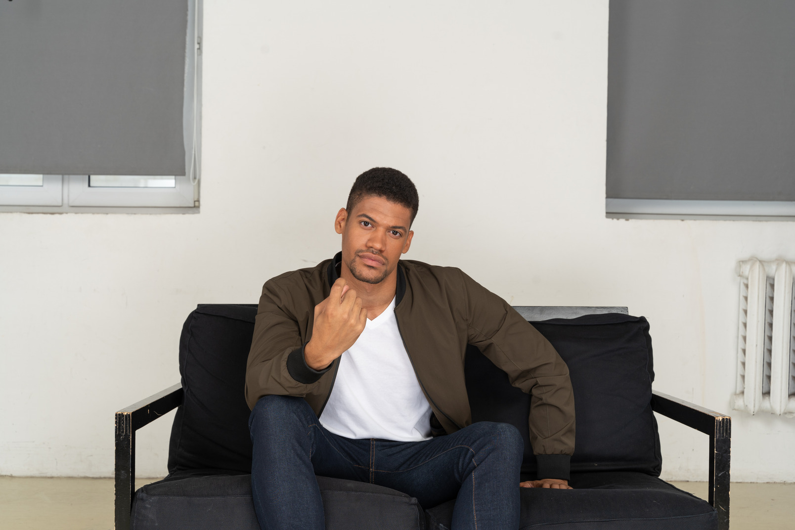 Young man sitting on the sofa and showing hand gesture