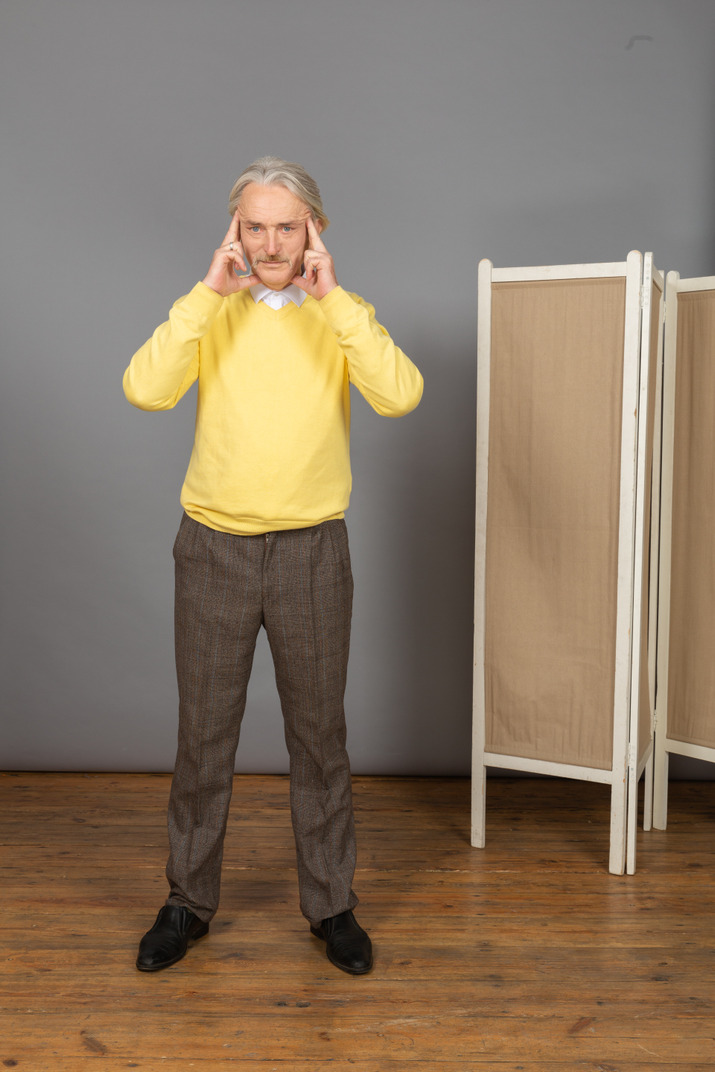 Front view of a concentrated old man touching his temples while looking at camera