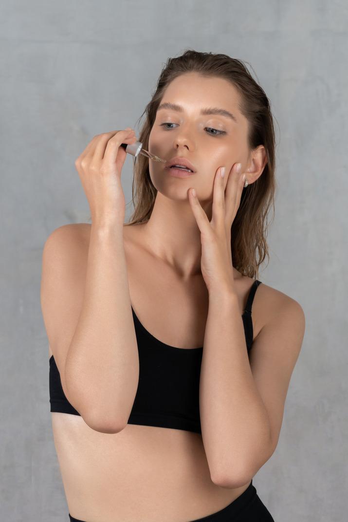 フェイスセラムを使用した若い女性の正面図