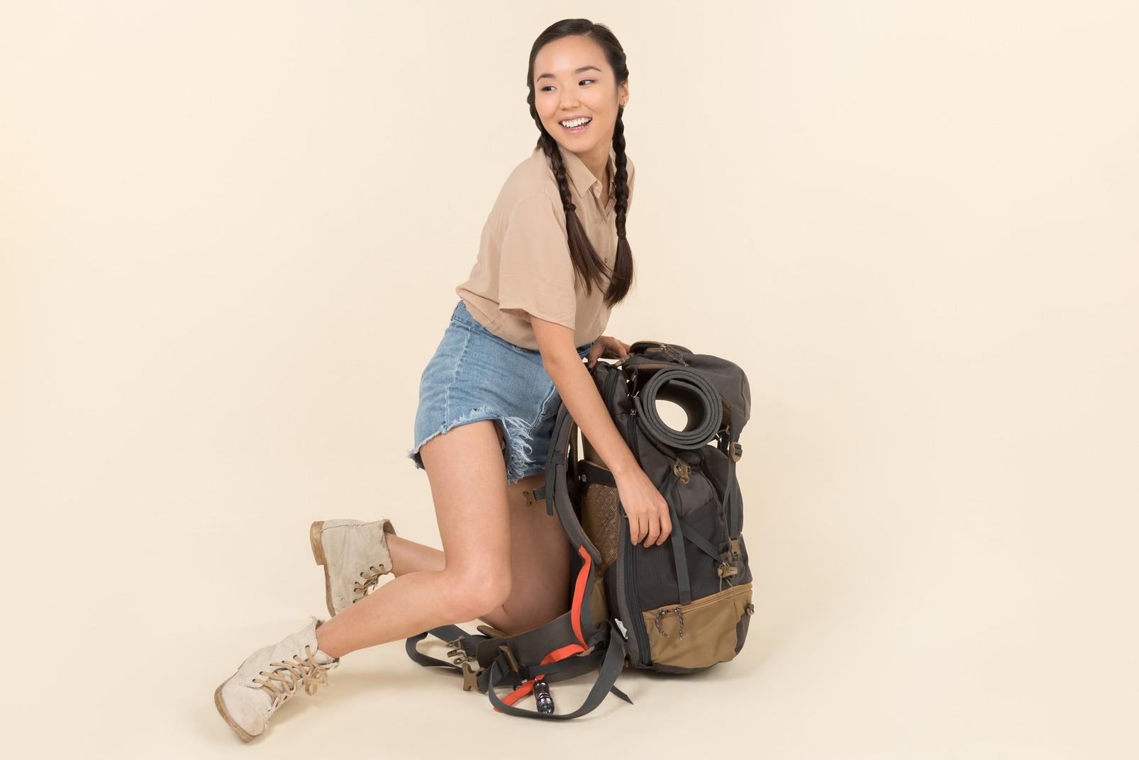 Young asian female traveller sitting near huge tourist backpack