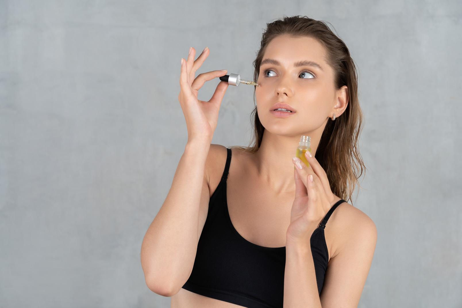 Vue de face d'une jeune femme utilisant un sérum pour le visage