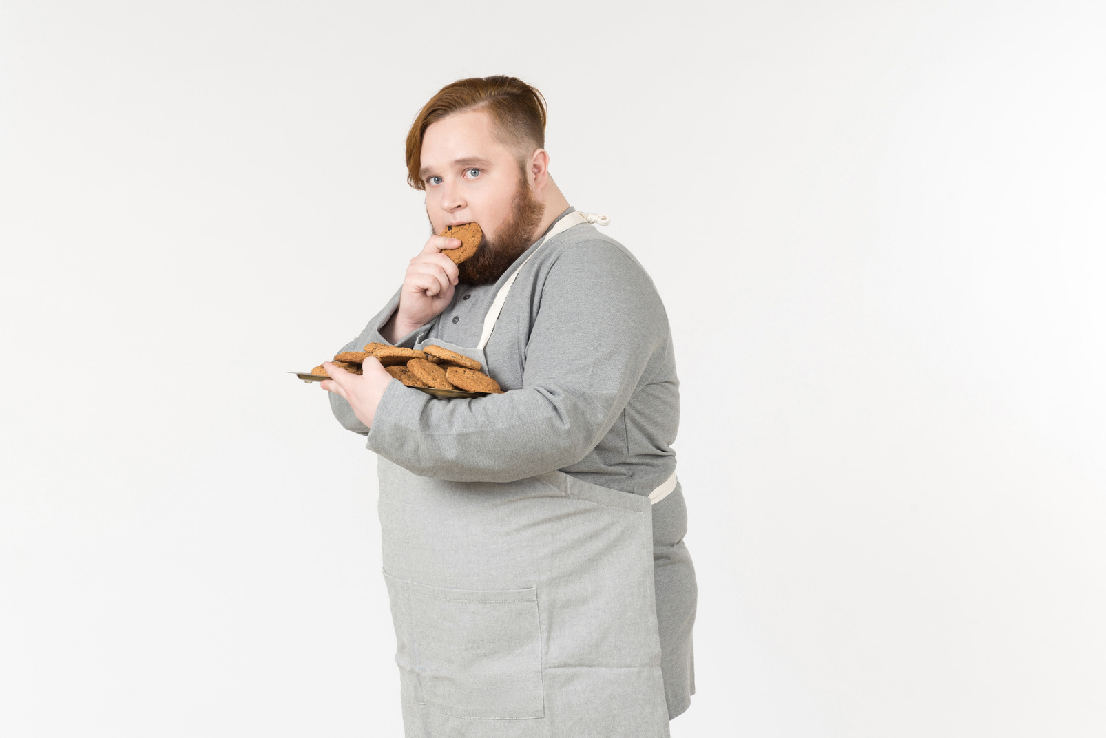 Taken by surprise fat man eating a cookie
