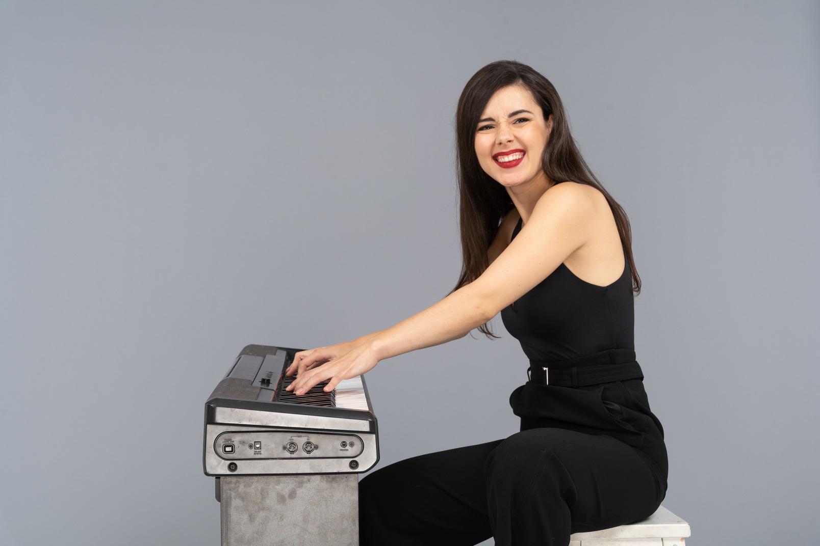 Seitenansicht einer lächelnden sitzenden jungen dame im schwarzen anzug beim klavierspielen
